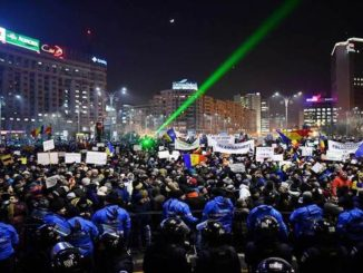 Romanian riot police stand guard as people demonstrate against controversial decrees to pardon corrupt politicians